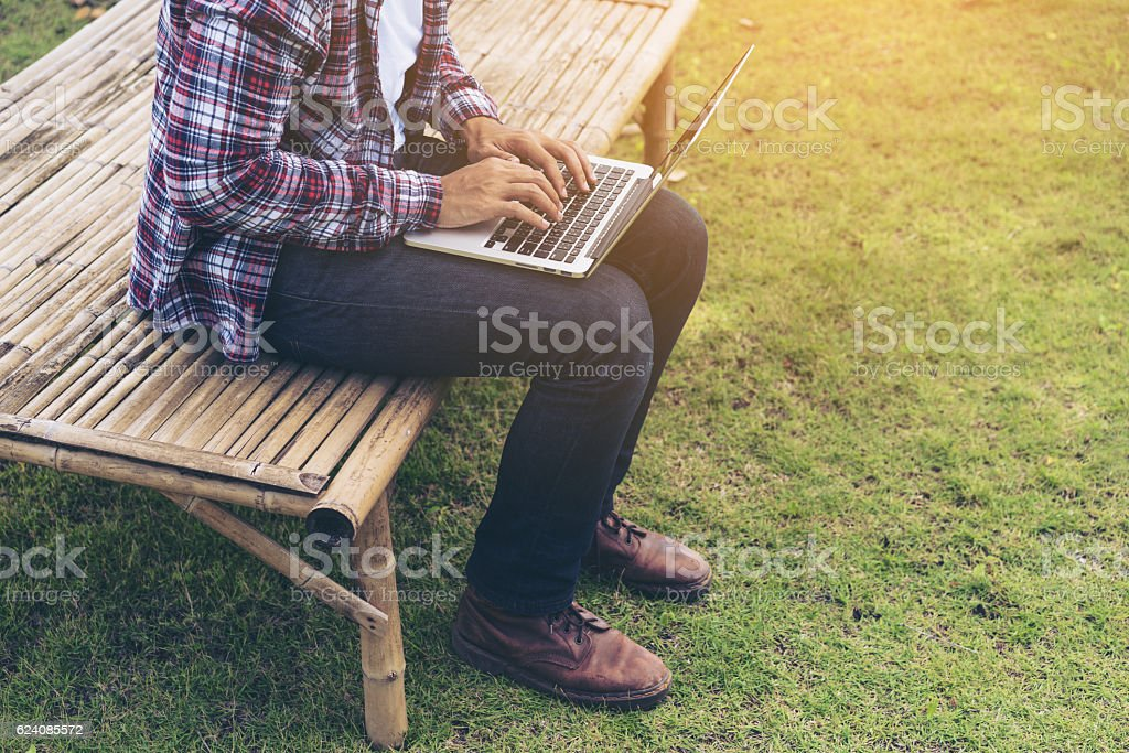 Man working on laptop. Nature background. stock photo