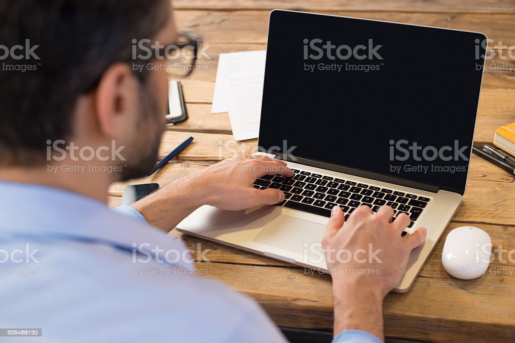 Back view of businessman sitting in front of laptop screen. Man...