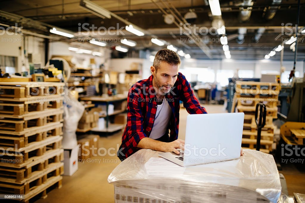 Photo of a man working on his laptop in printing factory