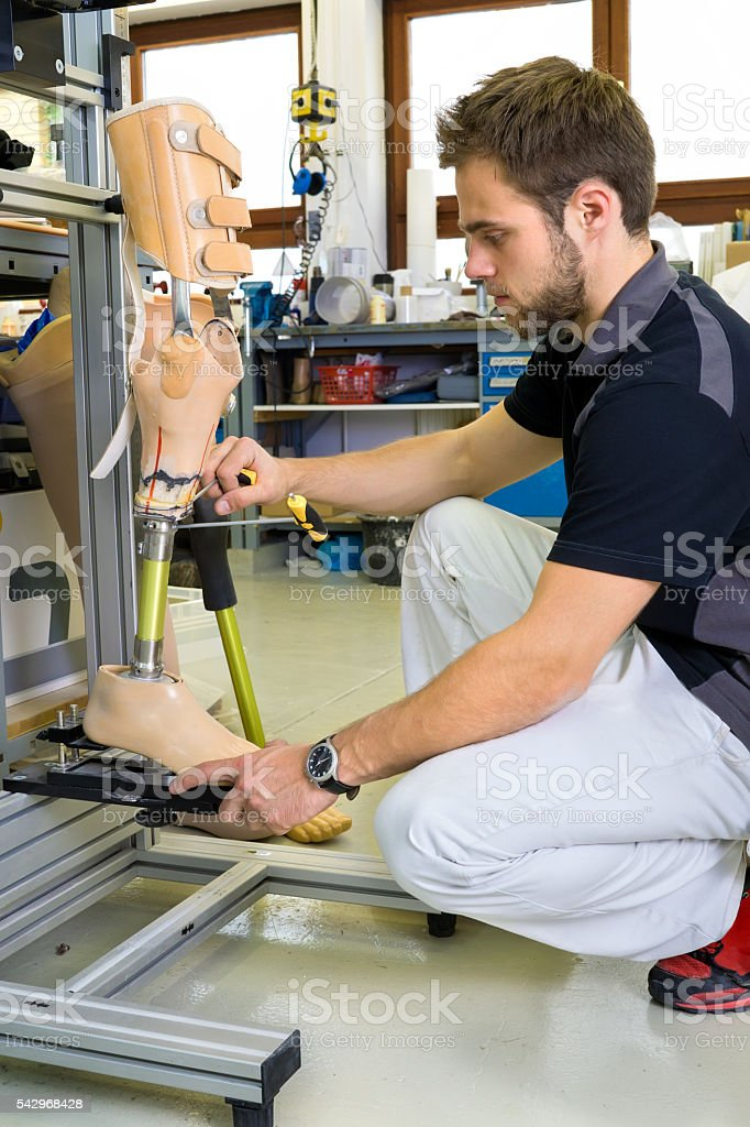 Man working on prosthetic leg assembly. stock photo