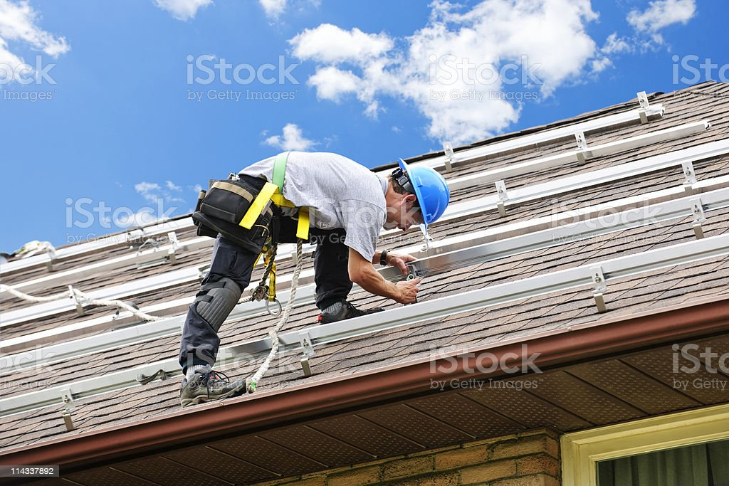 Man working on roof installing rails for solar panels stock photo