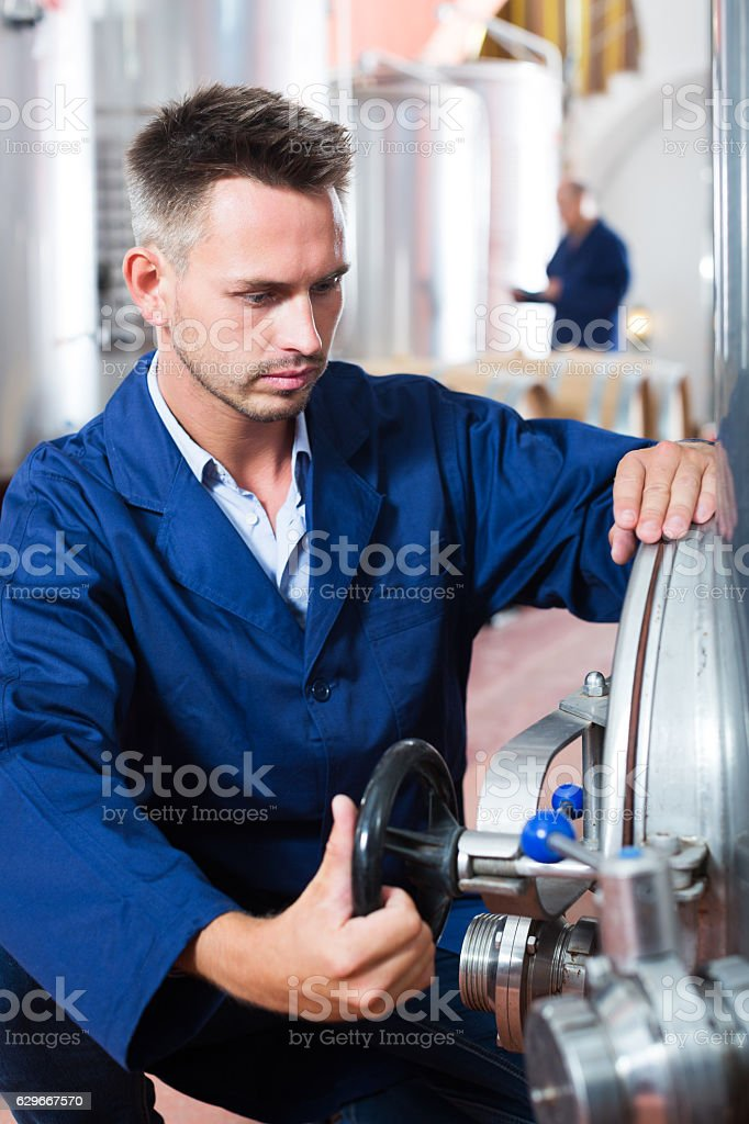 Man working on secondary fermentation equipment stock photo