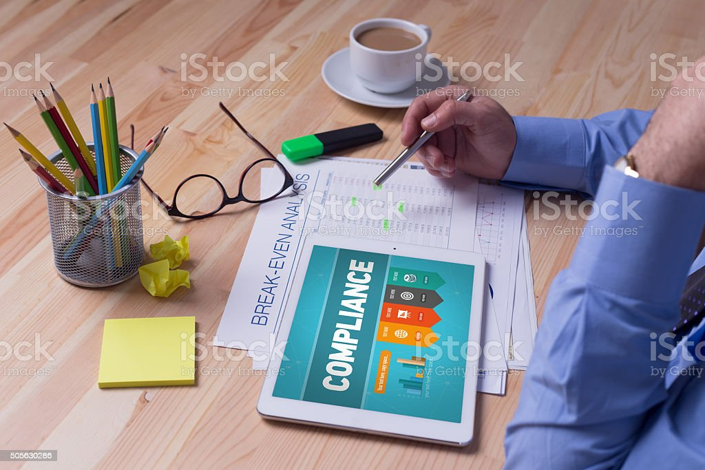 Man working on tablet with COMPLIANCE on a screen stock photo