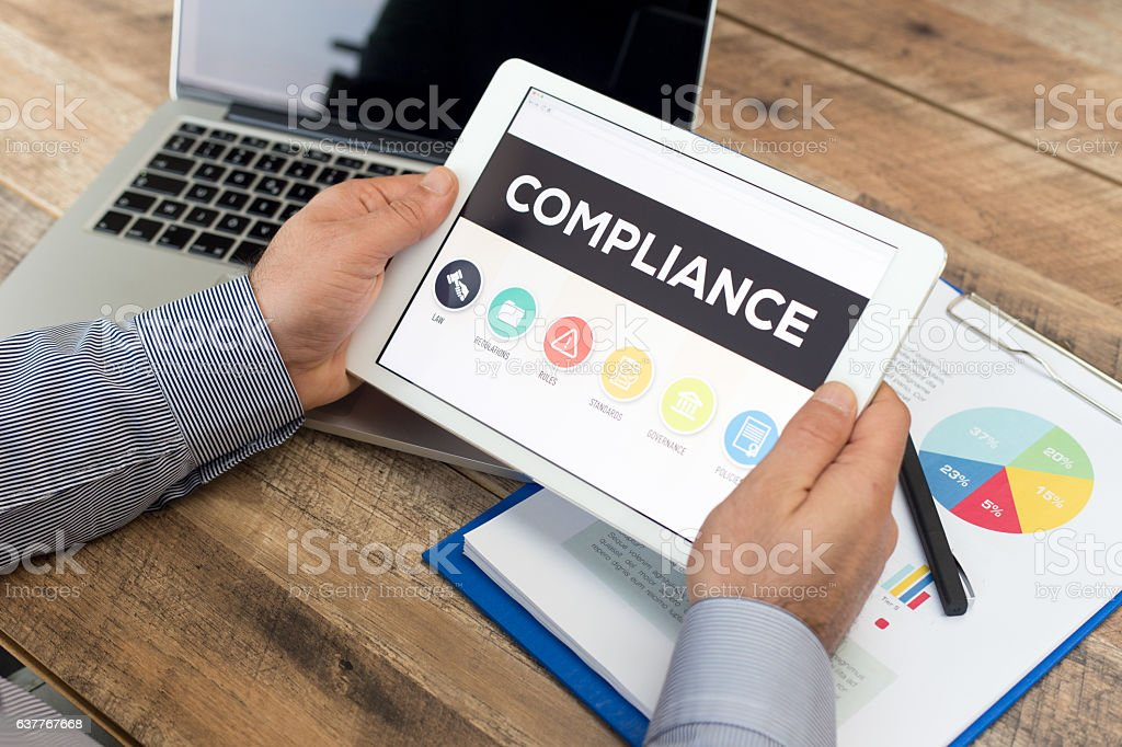 Man working on tablet with Compliance on screen stock photo