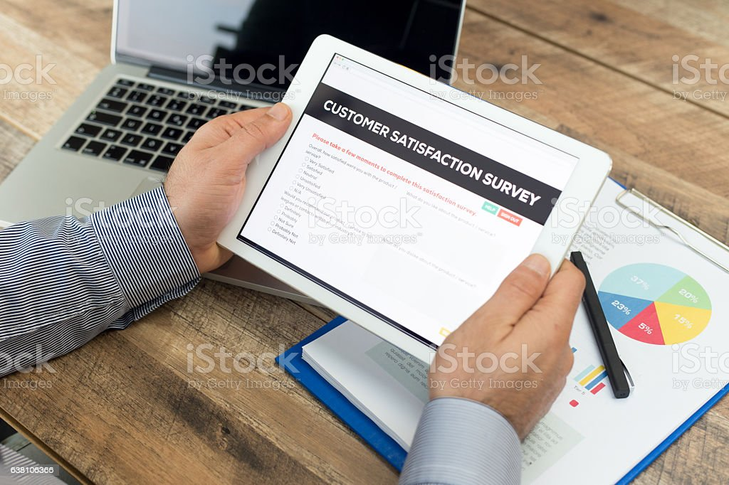 Man working on tablet with Customer Satisfaction Survey on screen stock photo