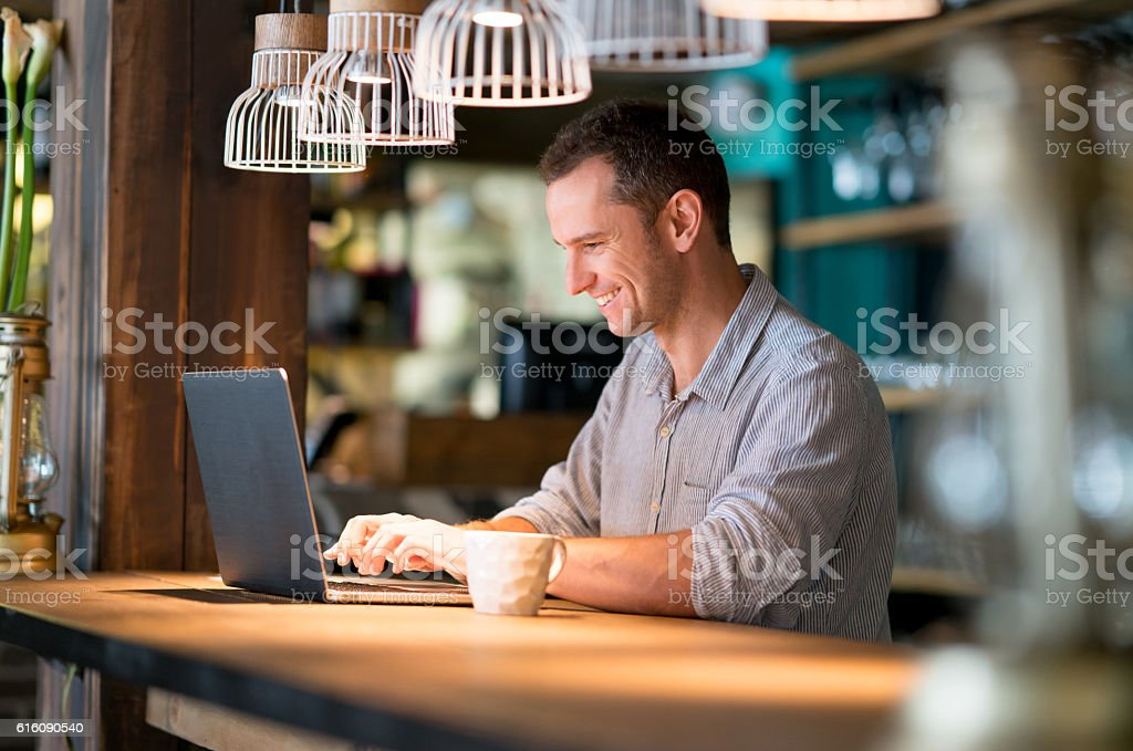 Man working online at a cafe stock photo