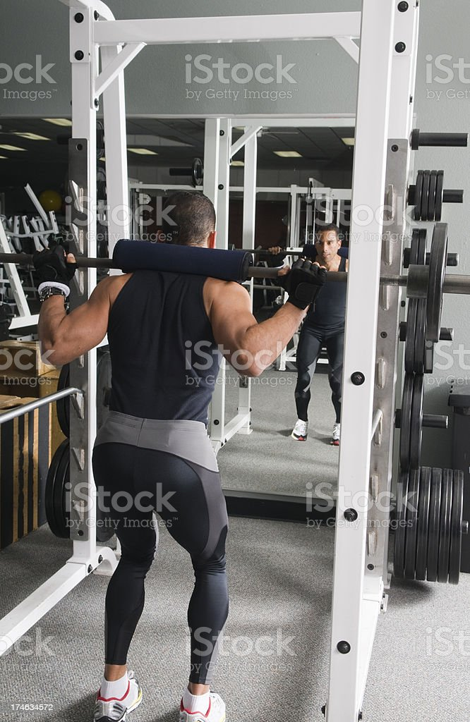 Man working out at gym with squat rack royalty-free stock photo