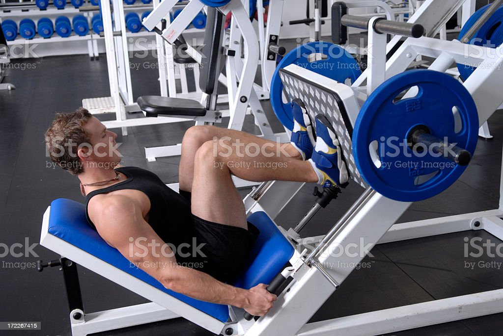 Man working out on a blue and white machine stock photo