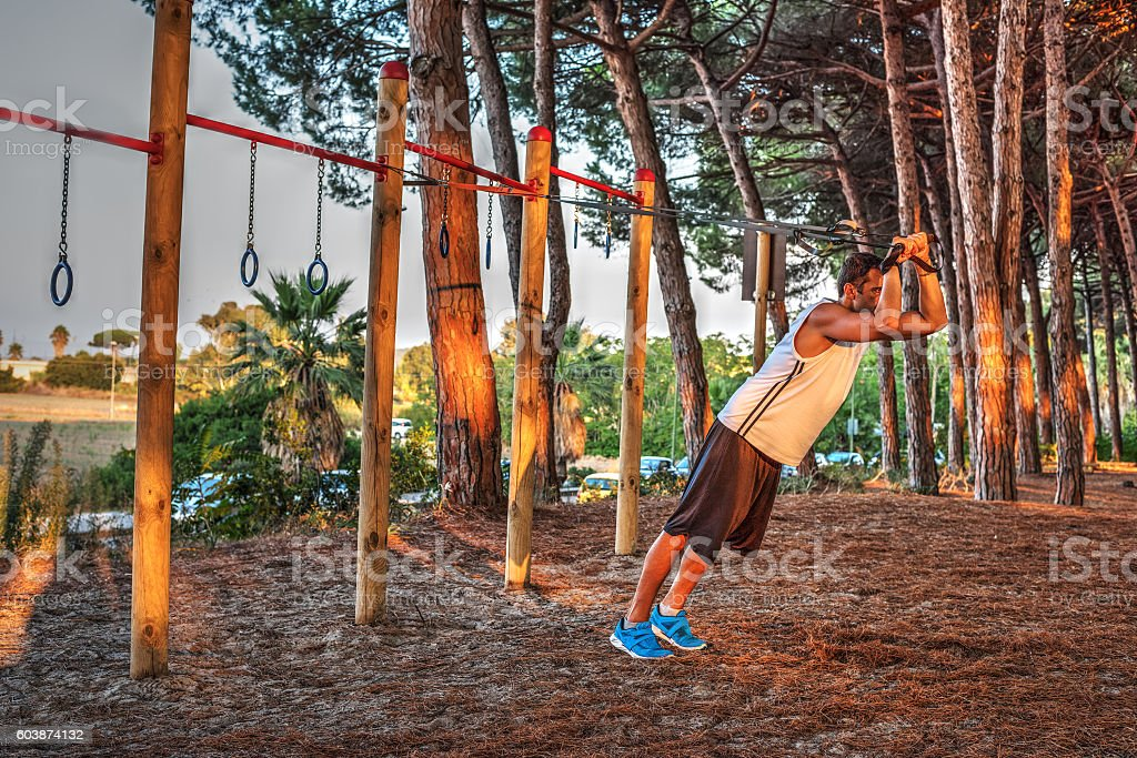 man working out with suspension straps stock photo