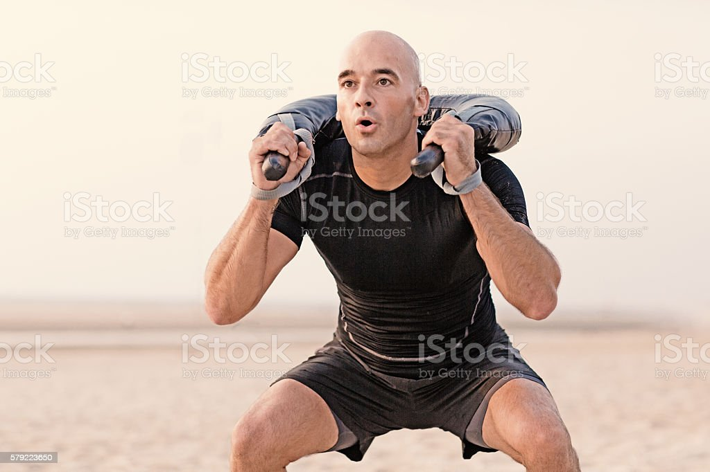 man working out with weights outdoors stock photo