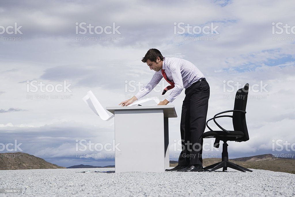 Man working outdoors with papers blowing in the wind royalty-free stock photo
