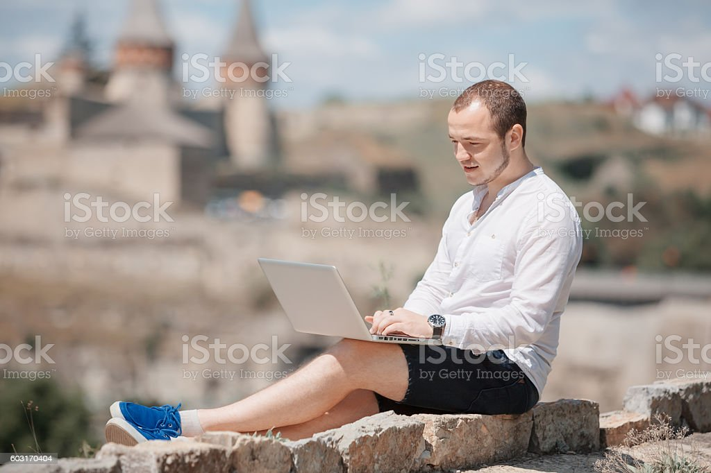 Man working sited on a stone wall stock photo