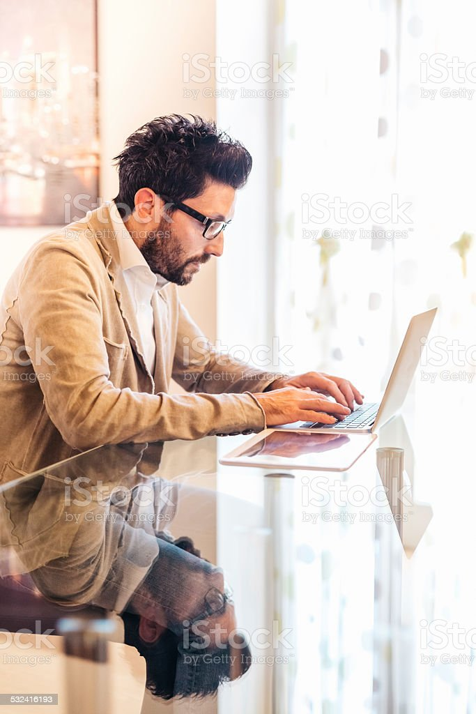 Man working using laptop at home stock photo