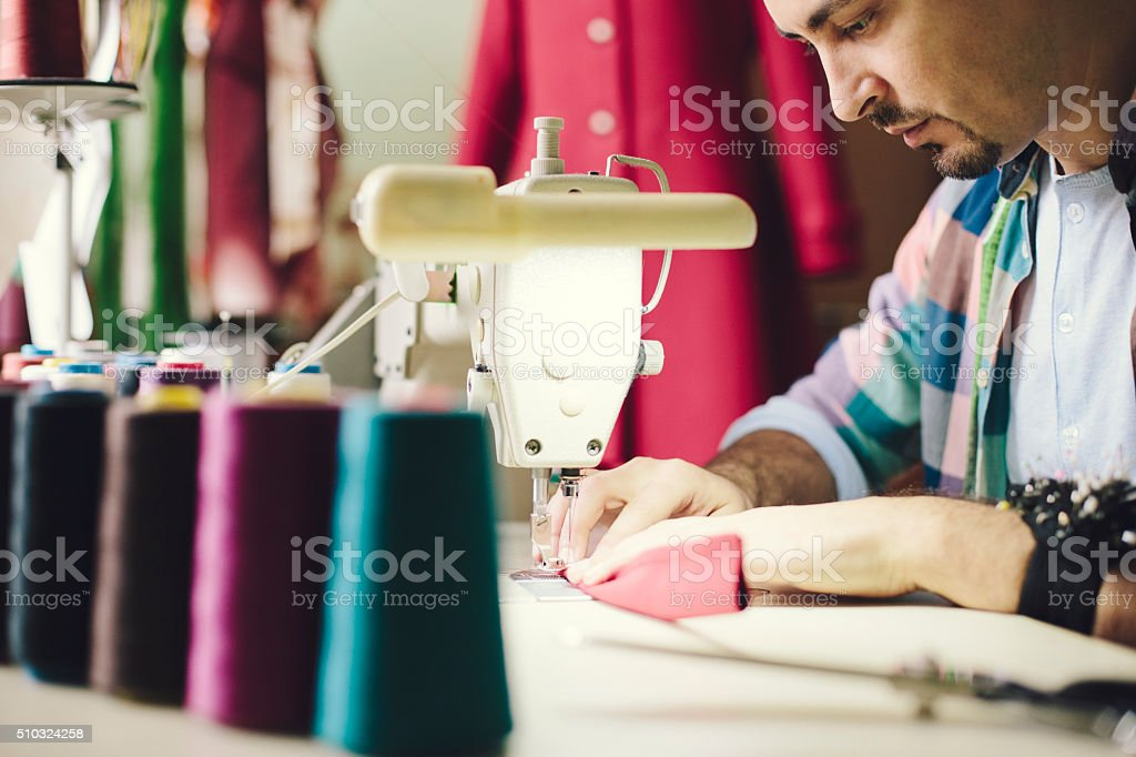 Man working with a sewing machine stock photo