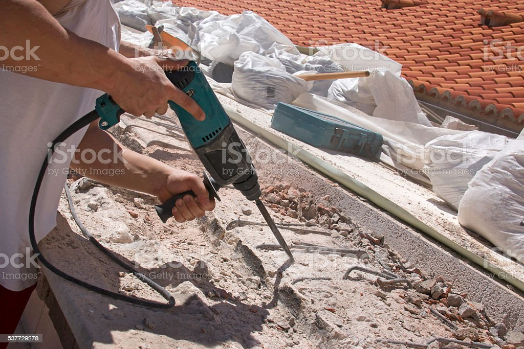 Man working with electric hammer stock photo