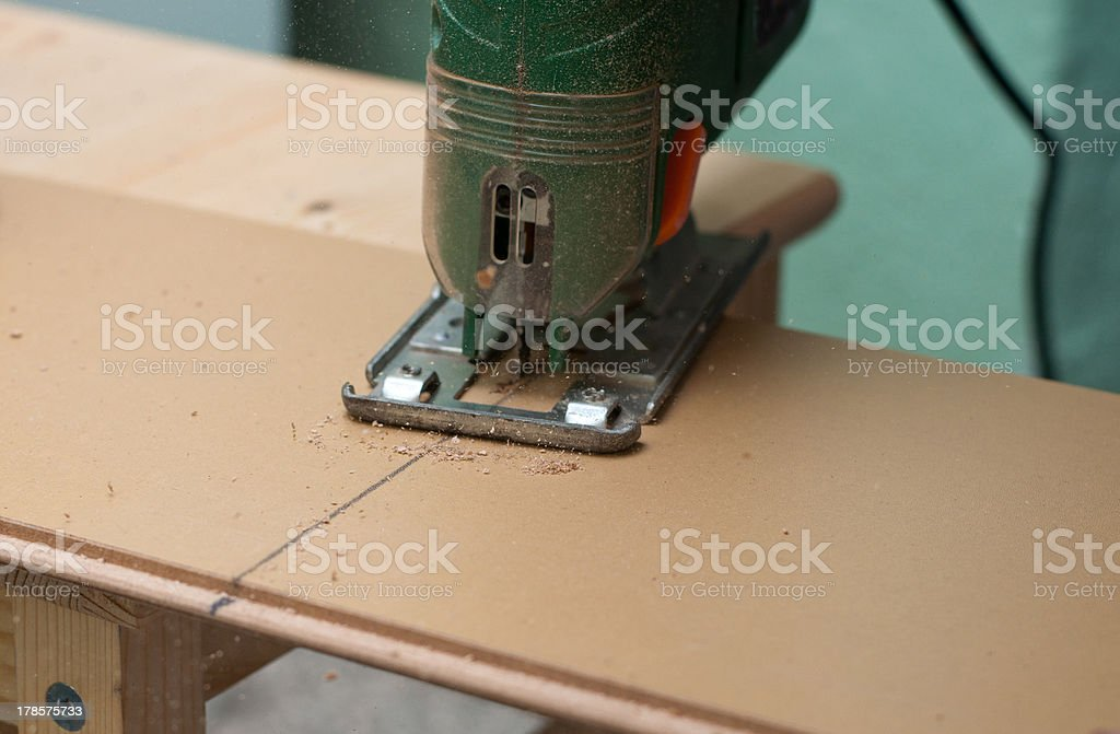Man working with jig saw stock photo