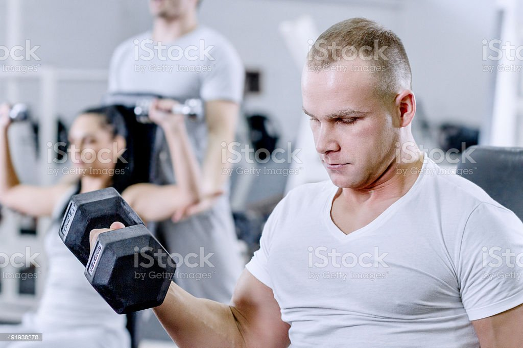Man Working With Weights In Gym stock photo