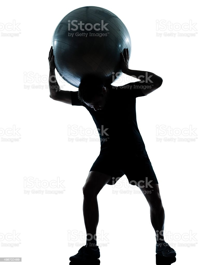 man workout holding fitness ball silhouette stock photo