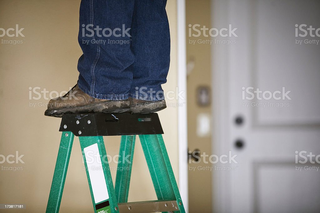 Man Works on Home Repair / Feet and Ladder stock photo