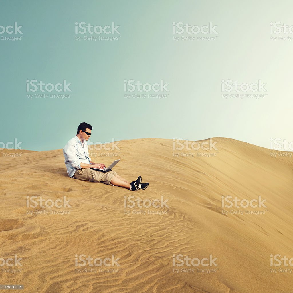 Man works on laptop in a desert stock photo