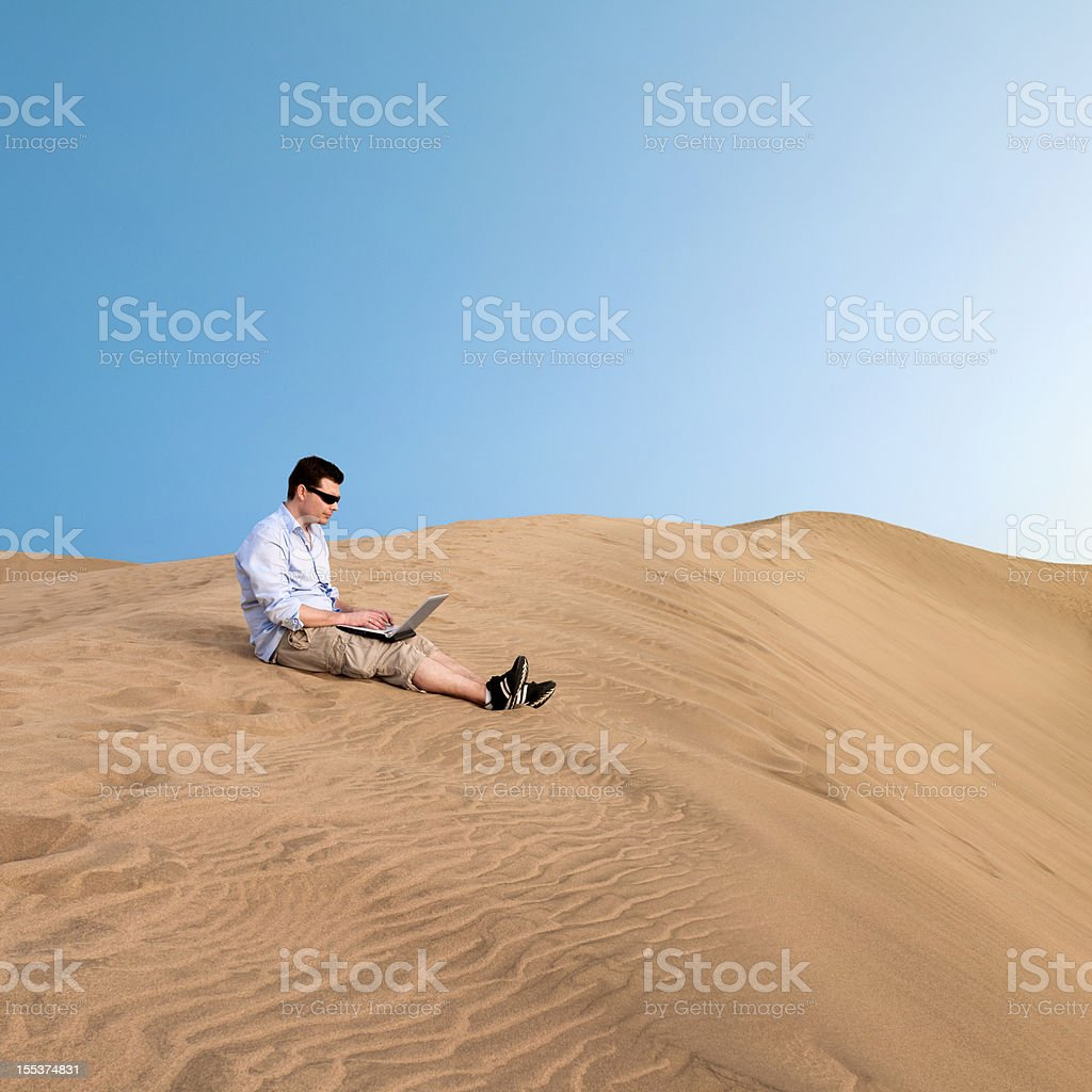 Man works on laptop in the desert royalty-free stock photo