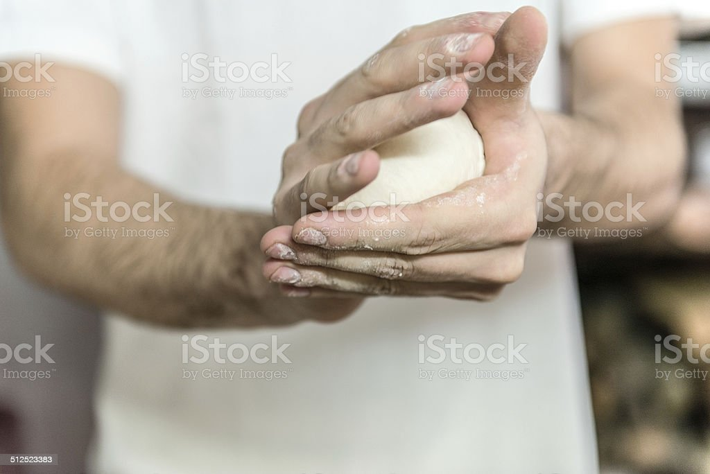 Man works on leavened pizza dough stock photo