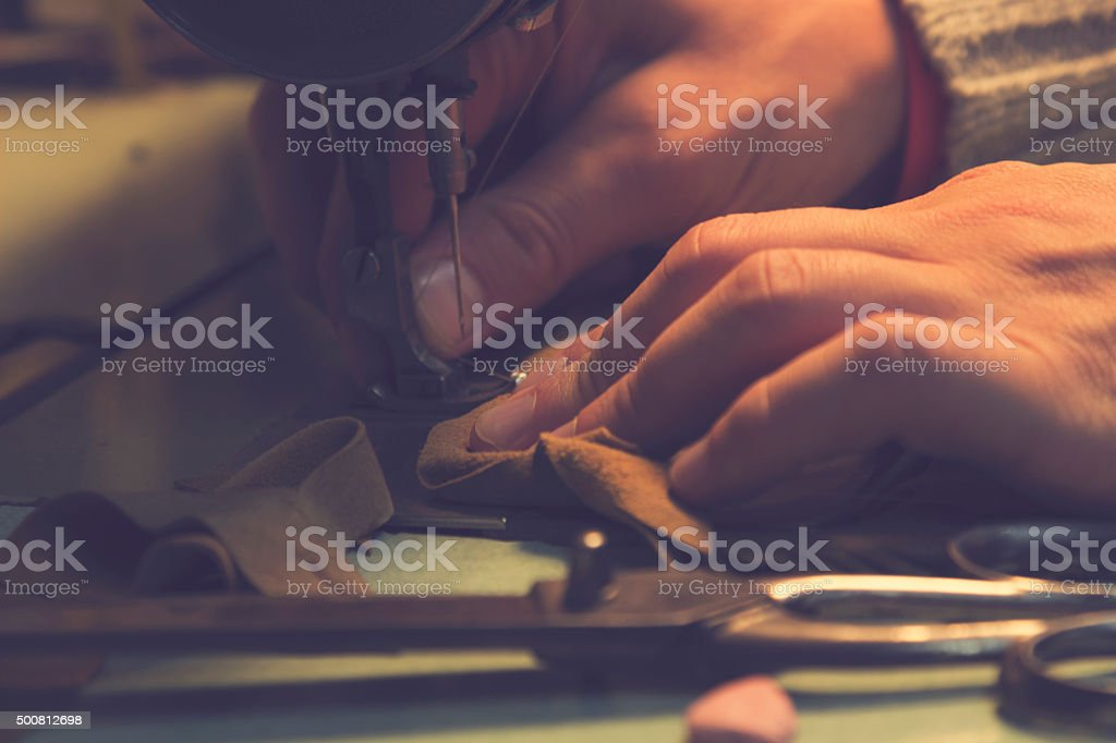 Man works on sewing machine. stock photo