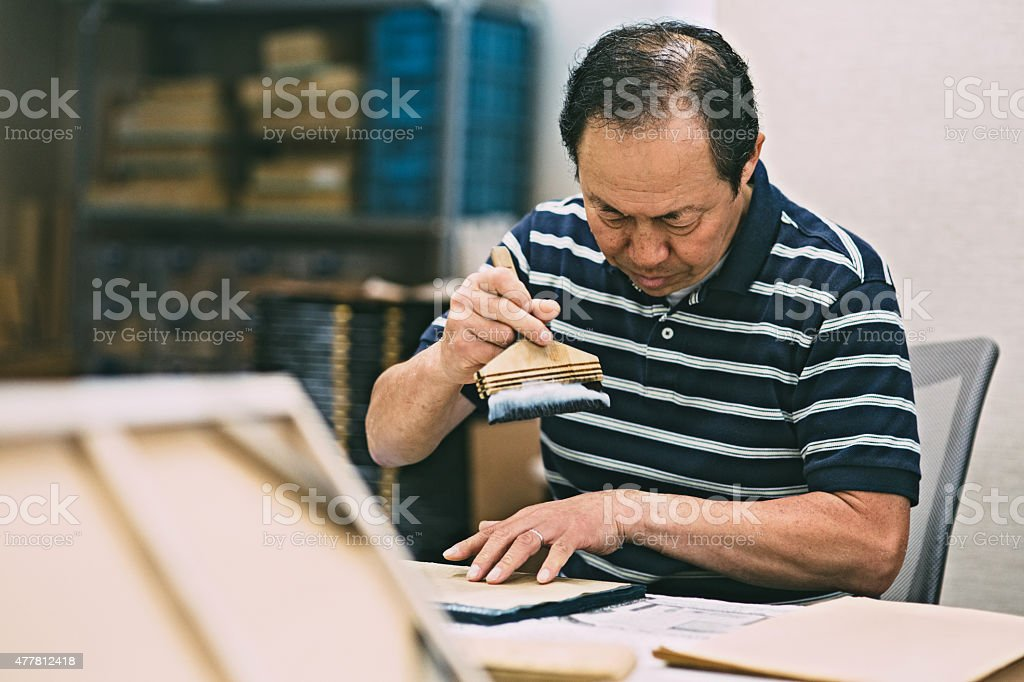 Man works on the wooden craft product stock photo