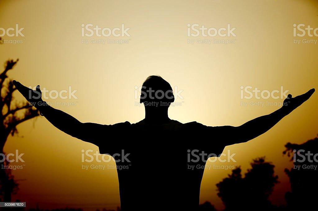 Man worshiping at sunset stock photo
