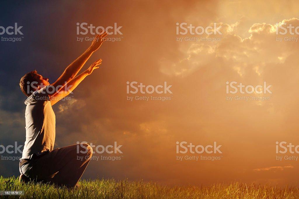Man worshipping God on the grass at sunrise stock photo