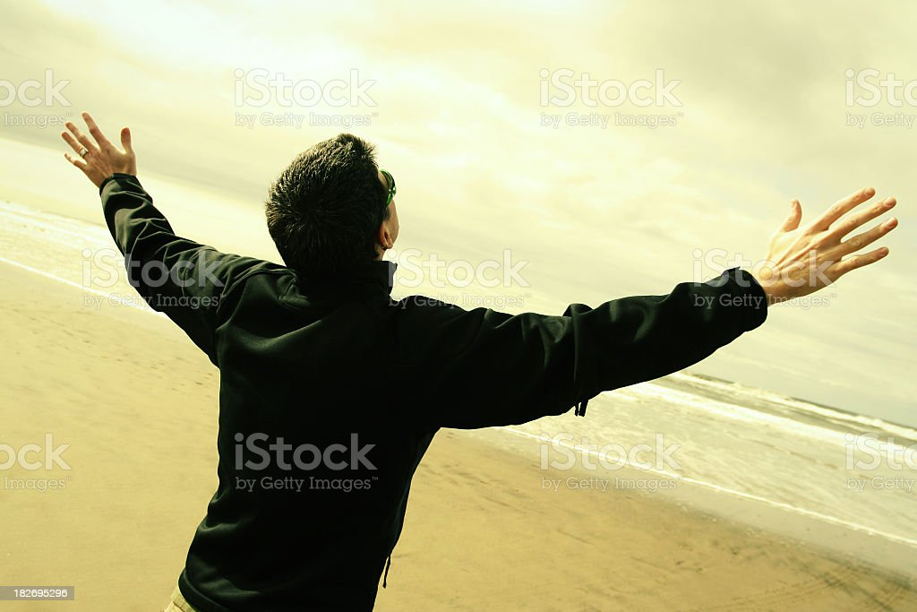 A man worshipping with his hands in the air on a beach royalty-free stock photo