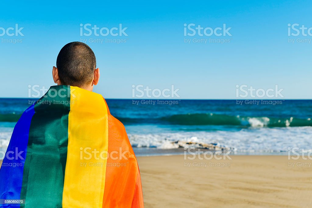 man wrapped in a rainbow flag stock photo