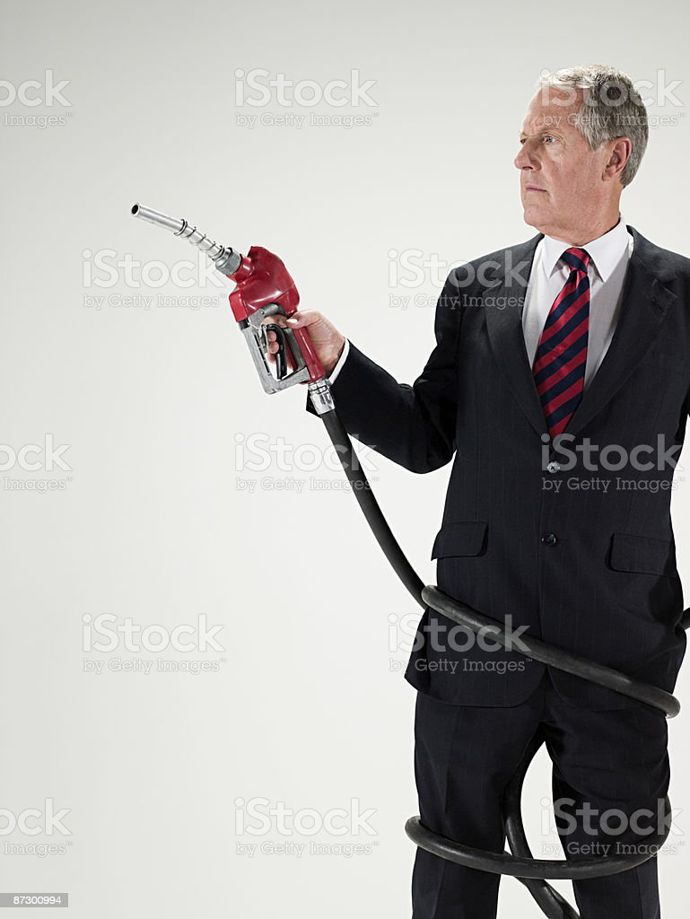 Man wrapped in fuel pump hose royalty-free stock photo