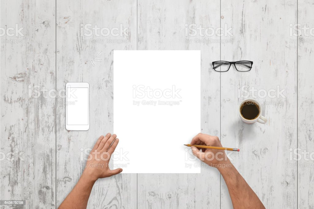 Man write on empty paper on white wooden desk. White smart phone with isolated screen for mockup. Glasses and cup of coffee beside. stock photo