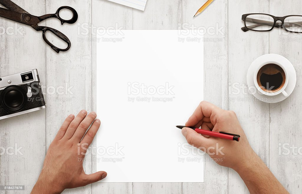 Man write with red pen on isolated, white paper. Coffee stock photo