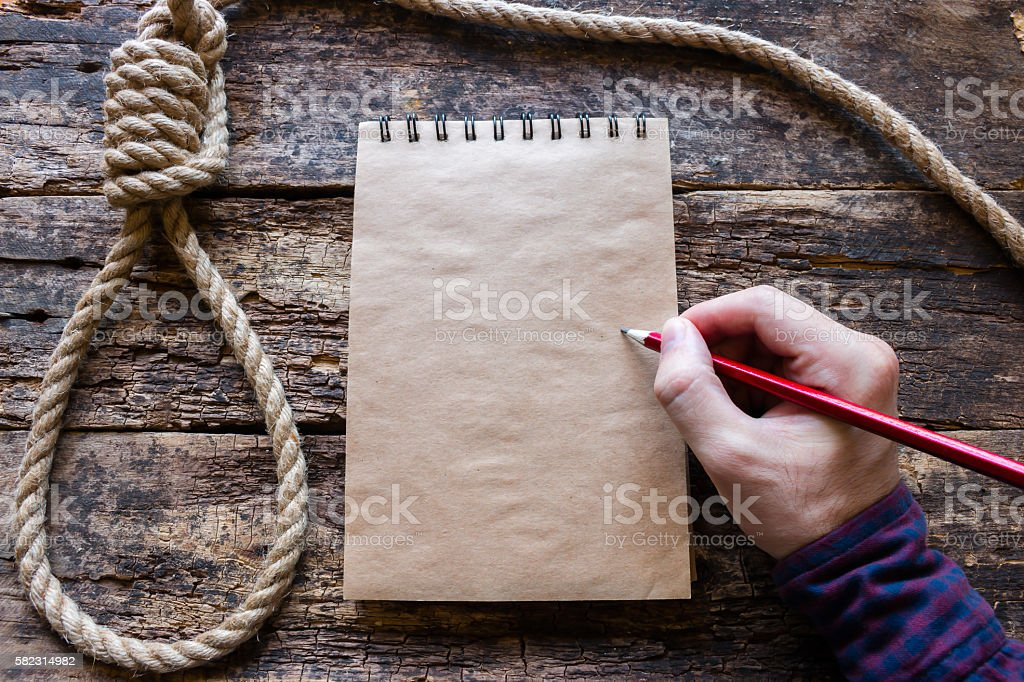 man writes a suicide note in the notebook stock photo