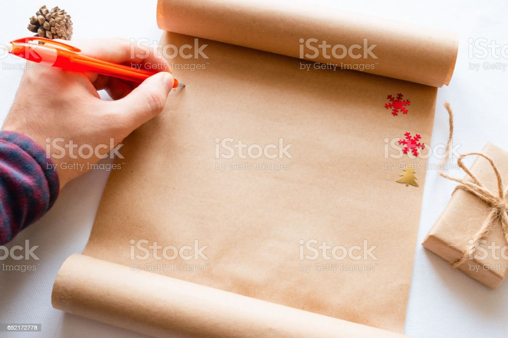 man writes in the scroll beside a Christmas present stock photo