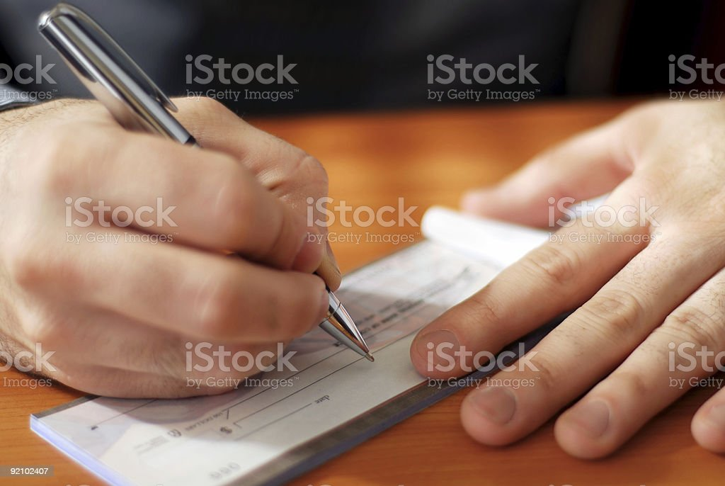 Man writing a check stock photo