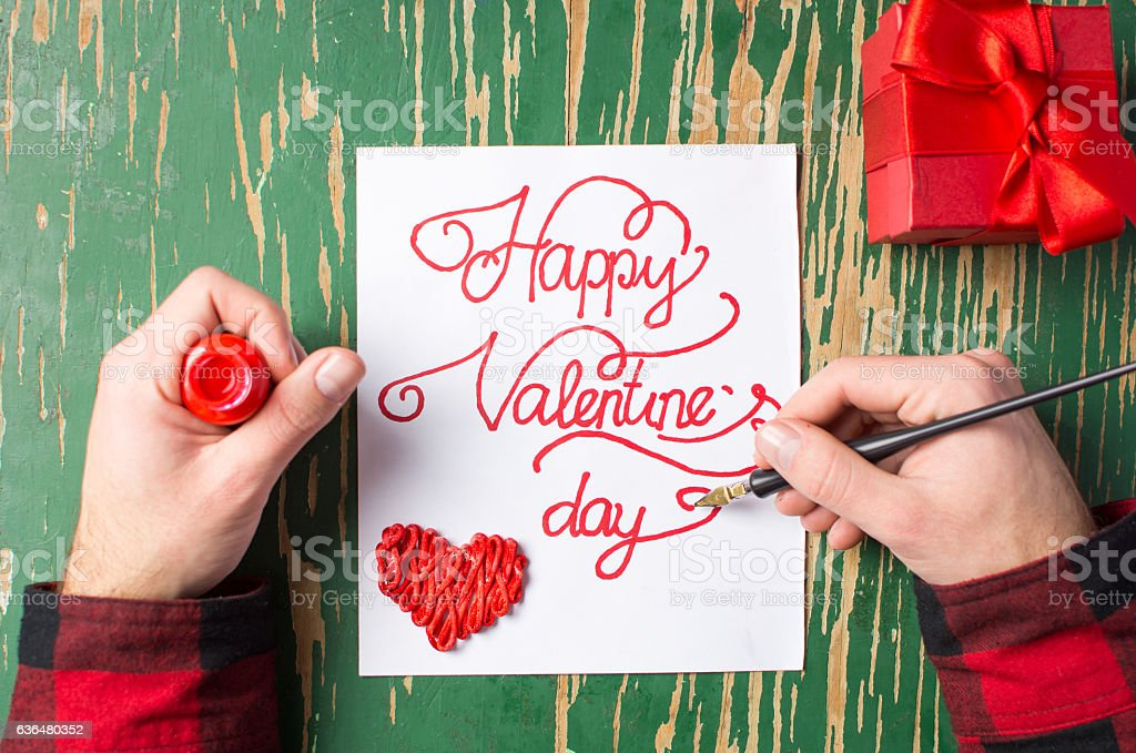 Man writing a Valentines day card and preparing present stock photo