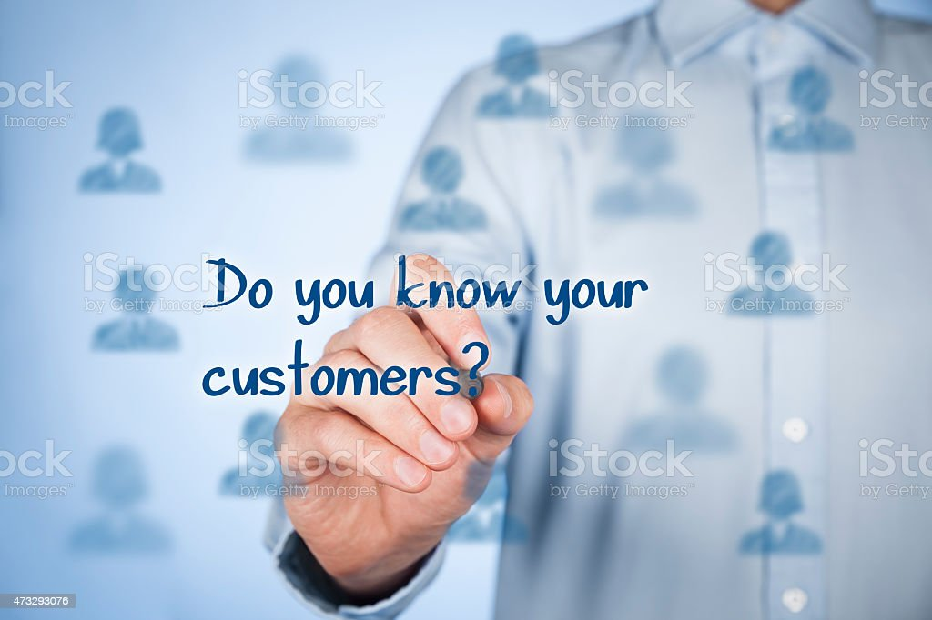 Man writing Do you know your customers? on a clear wall stock photo
