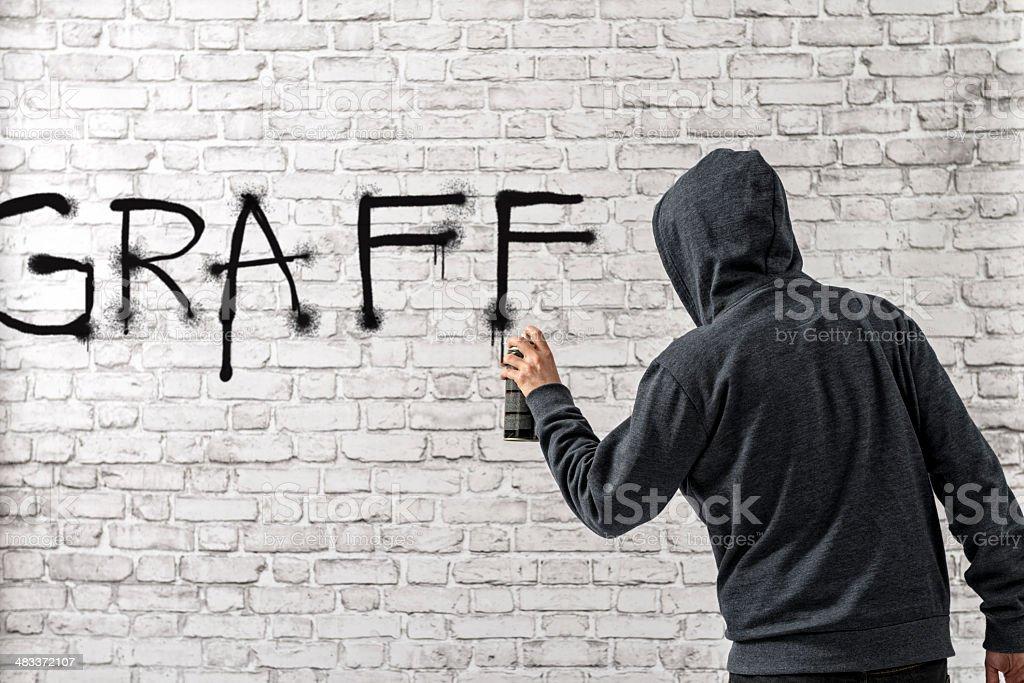 Man writing graffiti word with spray on white brick wall stock photo
