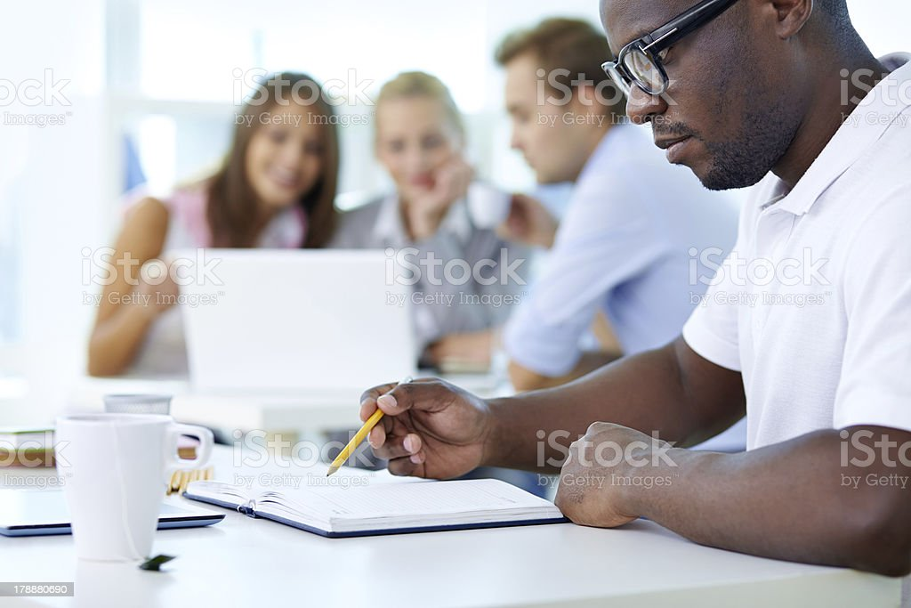 Man writing in a notebook while drinking tea stock photo