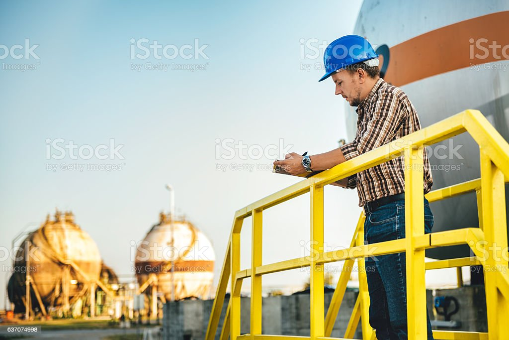 Man writing notes in the factory stock photo