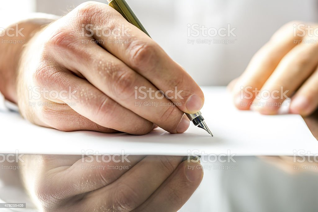 Man writing on a blank paper stock photo