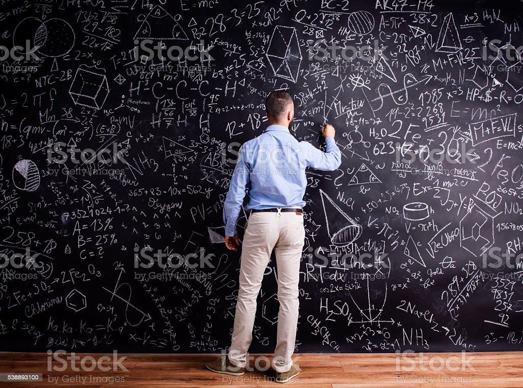 Man writing on big blackboard with mathematical symbols stock photo
