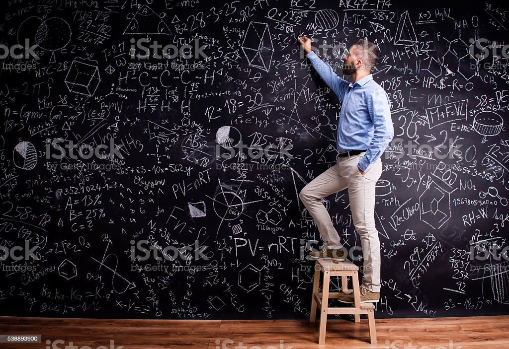 Man writing on big blackboard with mathematical symbols stock photo