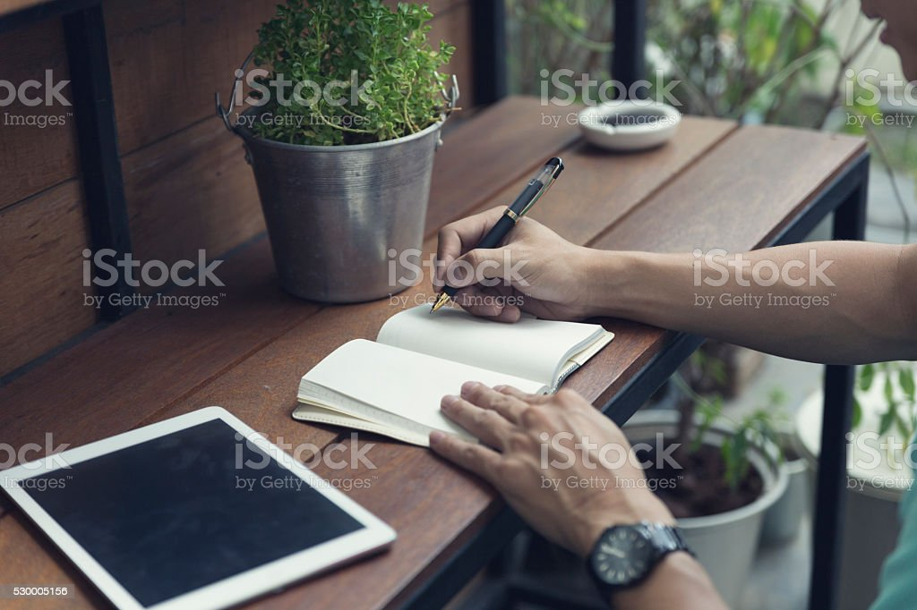man writing on notebook with digital tablet stock photo