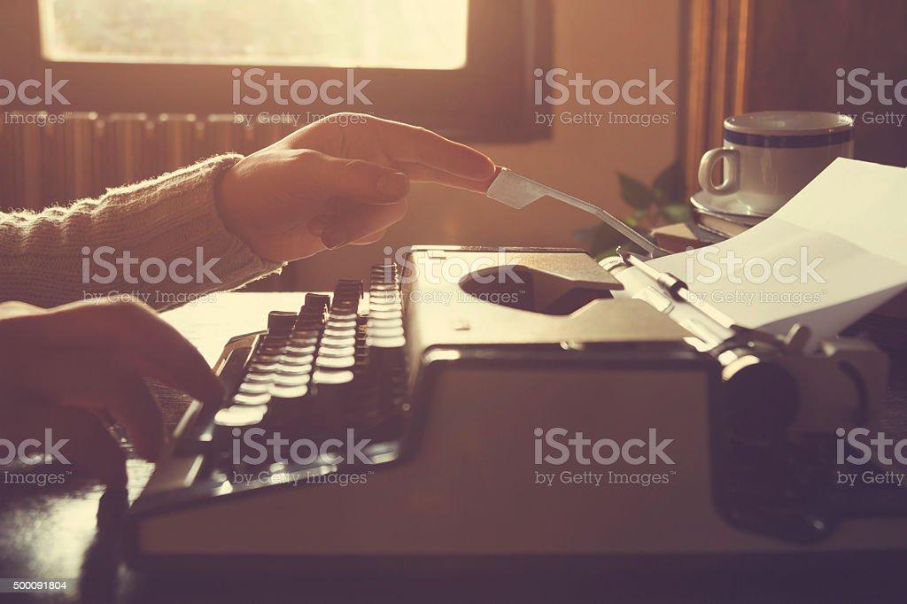 Man writing on old typewriter. stock photo