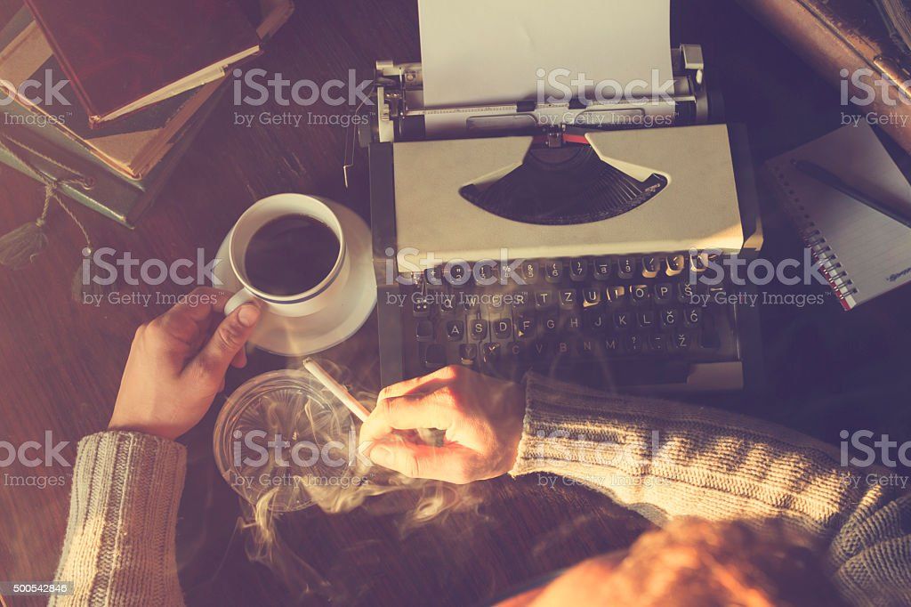 Man writing on old typewriter. stock photo
