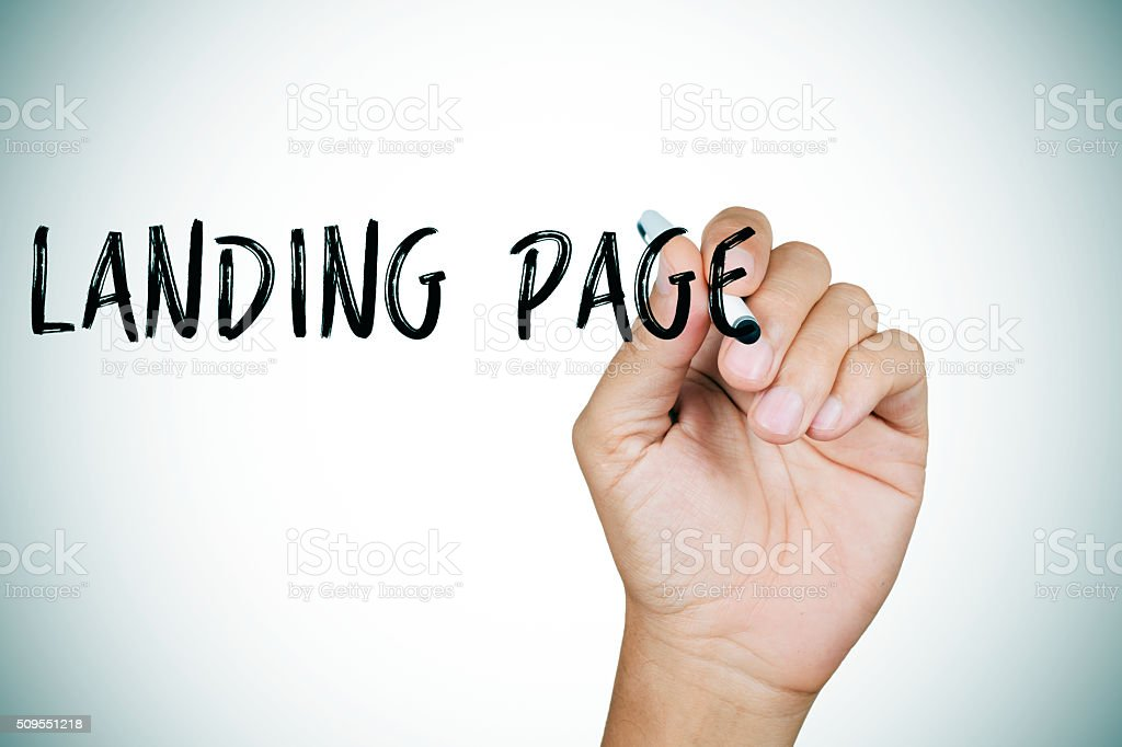 man writing the text landing page stock photo